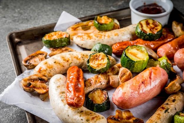 Grill. asortyment różnych kiełbas mięsnych z grilla, z warzywami bbq - pieczarki, pomidory, cukinia, cebula. na czarnym kamiennym stole, na blasze do pieczenia z sosem. skopiuj miejsce