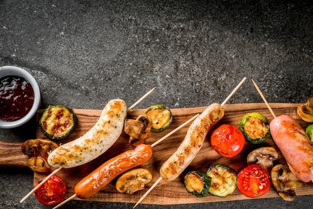 Grill. asortyment różnych kiełbas mięsnych z grilla, z warzywami bbq