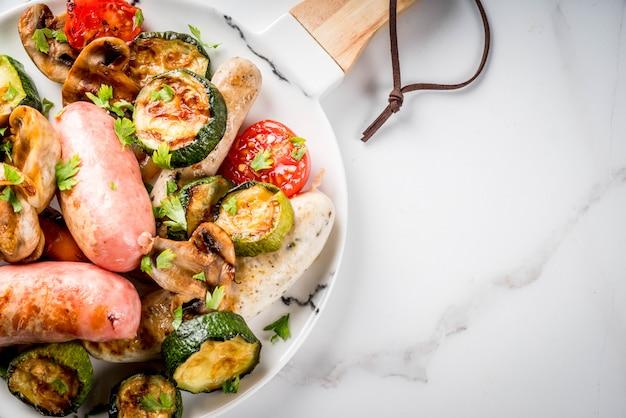 Grill. asortyment różnych kiełbas mięsnych z grilla, z warzywami grzyby bbq, pomidory, cukinia, cebula. na białym marmurowym stole, na talerzu, z sosem. widok z góry lato