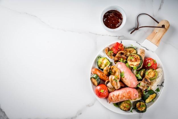 Grill. asortyment różnych kiełbas mięsnych z grilla, z warzywami, pieczarkami z grilla, pomidorami, cukinią, cebulą. na białym marmurowym stole, na talerzu, z sosem. widok z góry lato
