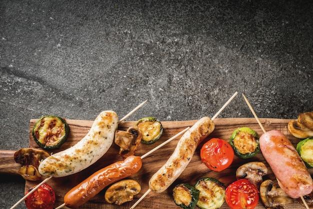 Grill. asortyment różnych kiełbas mięsnych z grilla, z warzywami, pieczarkami z grilla, pomidorami, cukinią, cebulą. na czarnym kamiennym stole, na talerzu do krojenia, z sosem. widok z góry lato