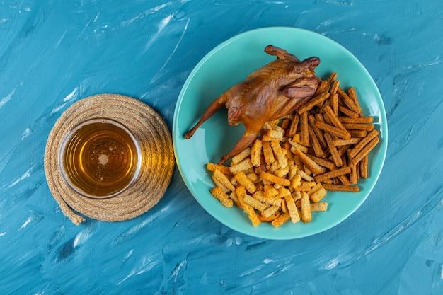 Grill i grzanki na talerzu obok kufla, na niebieskiej powierzchni.