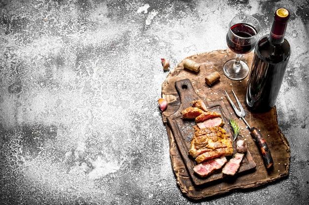 Grill mięsny. plasterki wieprzowiny z czerwonym winem na drewnianej tacy na rustykalnym stole.