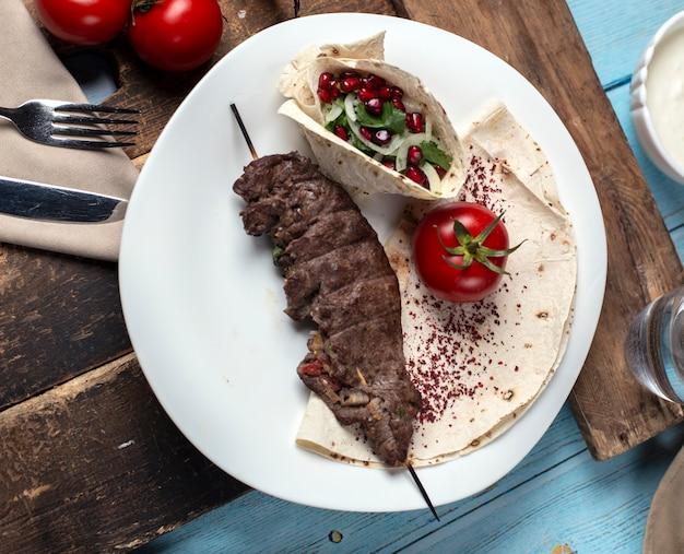 Grill mięsny podawany z sałatką warzywną podawany w lawaszu