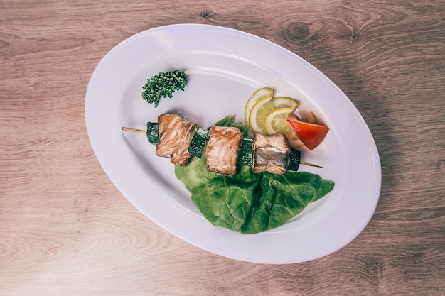 Grill na drewnianych szaszłykach z plasterkami cytryny i świeżymi warzywami. dania na piknik