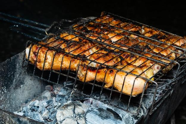 Grill na ogniu, gorące węgle, grillowane mięso z kurczaka