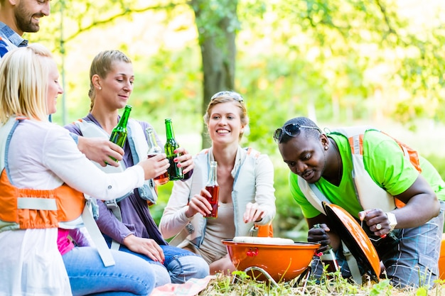 Grill przyjaciół w lesie pije piwo
