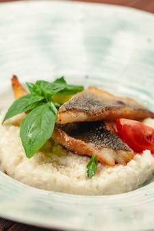 Grill rybny danie pieczone w całości z grilla na talerzu z warzywami i cytryną