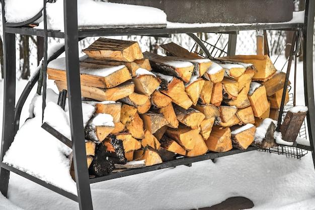 Grill w zaspie. posiekane drewno opałowe z sosny i brzozy na grilla pod śniegiem na ulicy. czekanie na wiosnę