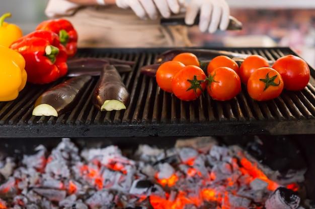 Grill wegetariański - świeża cała czerwona i żółta papryka na grillu z połówkową cukinią i całymi pomidorami zapiekana na gorącym węglu z grilla