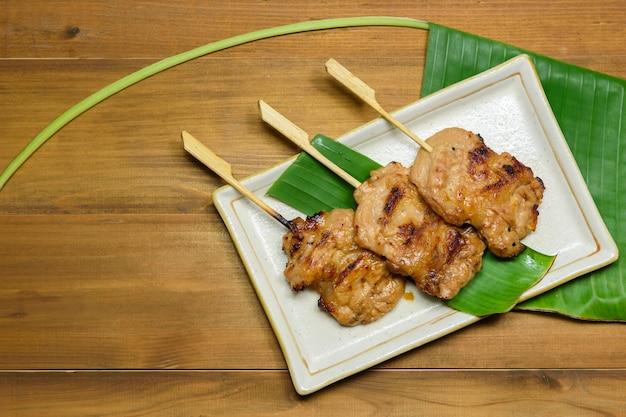Grill wieprzowy w stylu tajskim (wieprzowina z grilla) na talerzu z zielonym liściem bananowca na drewnianym stole, tajskie lokalne jedzenie
