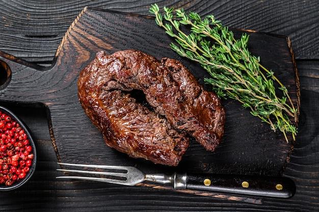 Grill z grilla wiszący stek tender na drewnianej desce do krojenia. ciemne drewniane tło. widok z góry.