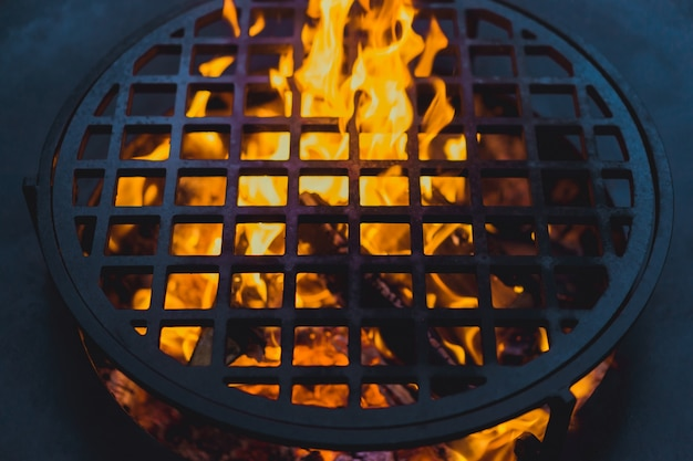 Grill z grilla, zbliżenie. profesjonalnie gotować jedzenie na otwartym ogniu na ruszcie żeliwnym.