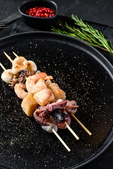 Grill z owocami morza. kebab na drewnianych szaszłykach z krewetkami, ośmiornicą, kalmarami i małżami. czarne tło. widok z góry