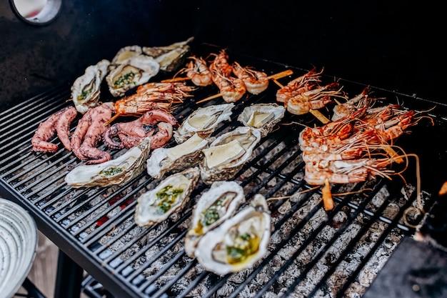 Grill z owocami morza. kolekcja ośmiornic, ostryg, małży, krewetek tygrysich grillowanych na grillu