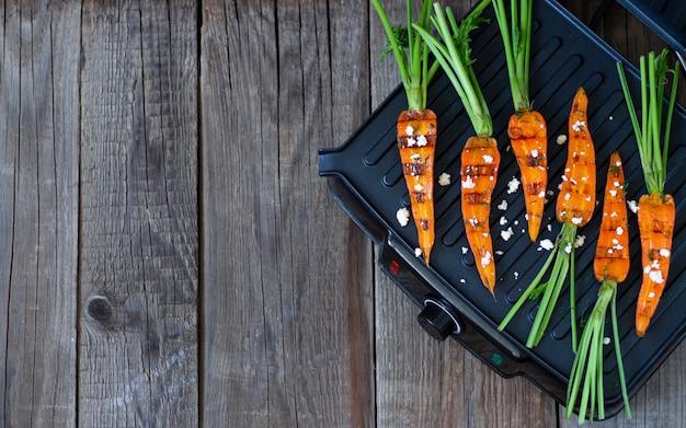 Grilla dziecka marchewki na grillu na nieociosanym drewnianym stołowym koszt stały z kopii przestrzenią