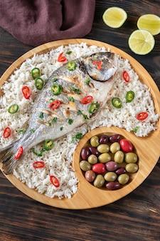 Grillowana dorada przyozdobiona białym ryżem i marynowanymi oliwkami
