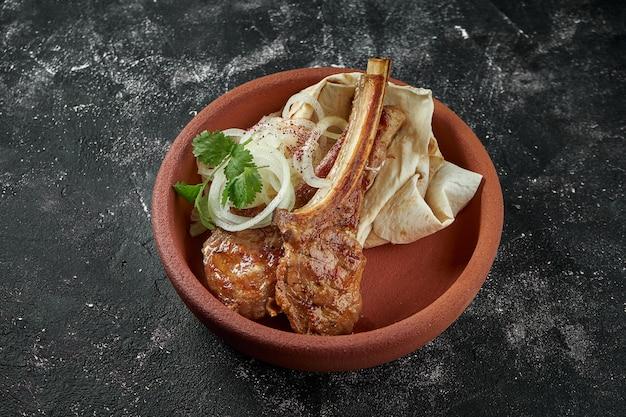 Grillowana jagnięcina z marynowaną cebulą, chleb pita w ceramicznej misce na ciemnym stole. zamknąć widok