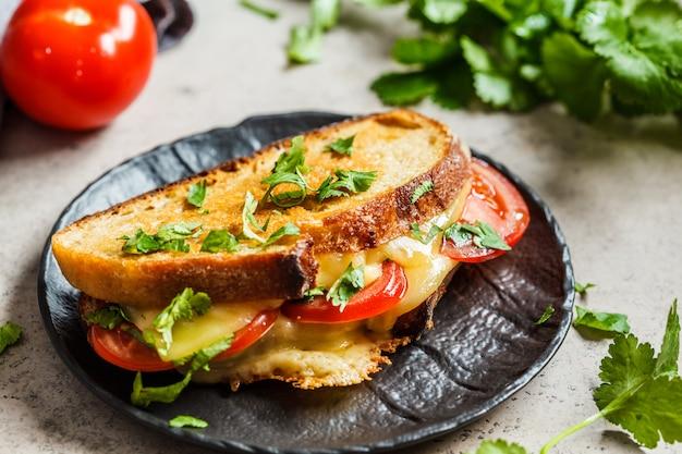 Grillowana kanapka z serem z pomidorem i zielenią, ciemne tło.
