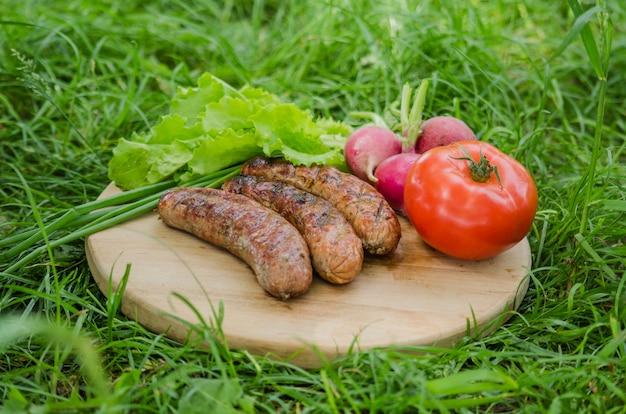 Grillowana kiełbasa i warzywa na starej drewnianej tacy
