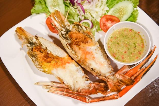 Grillowana krewetka pokrojona na pół z sosem ze świeżych warzyw i owoców morza, krewetka olbrzymia z grilla