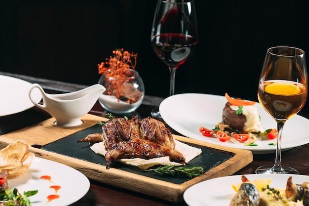 Grillowana kuropatwa, okoń morski, tartarus. różne potrawy na stole w restauracji.