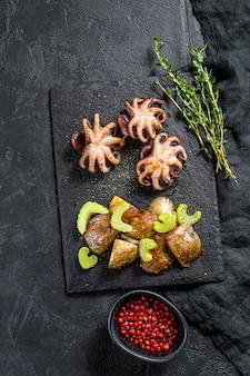 Grillowana ośmiornica. przystawka z pieczonymi ziemniakami i selerem. czarne tło. widok z góry. miejsce na tekst