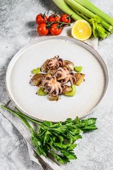 Grillowana ośmiornica z ziemniakami i selerem. szare tło. widok z góry