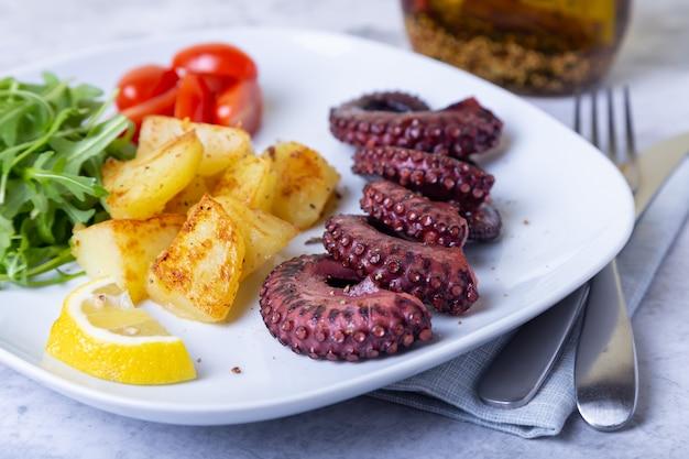 Grillowana ośmiornica ze smażonymi ziemniakami, rukolą, pomidorami i cytryną. zbliżenie.