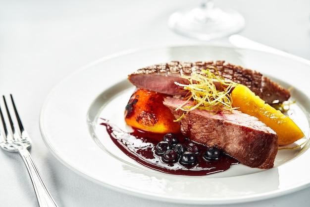 Grillowana pierś z kaczki z brzoskwiniami w sosie jagodowym, grillowany filet z kaczki na białym talerzu, zbliżenie mięsa kaczki z dodatkami deserowymi.