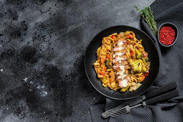 Grillowana pierś z kaczki z makaronem udon i warzywami. czarne tło.