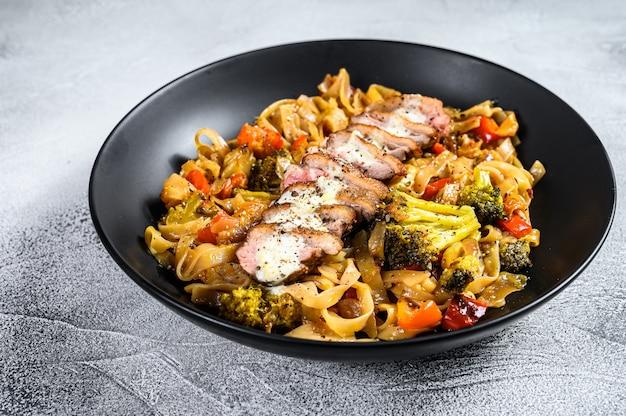 Grillowana pierś z kaczki z makaronem udon i warzywami. szare tło.