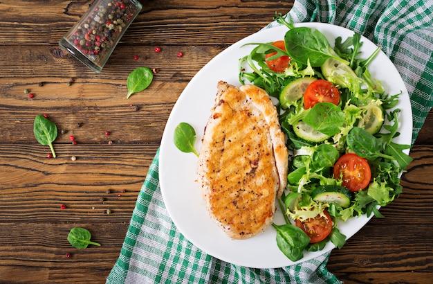 Grillowana pierś z kurczaka i sałatka ze świeżych warzyw - pomidory, ogórki i liście sałaty. sałatka z kurczakiem zdrowe jedzenie. leżał płasko. widok z góry