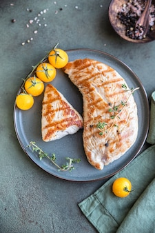 Grillowana pierś z kurczaka lub indyka z pomidorkami koktajlowymi i tymiankiem na talerzu ceramicznym