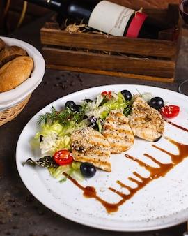 Grillowana pierś z kurczaka podawana z sałatką warzywną i oliwkami