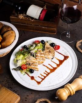 Grillowana pierś z kurczaka podawana z sałatką warzywną, oliwkami i lampką wina 1