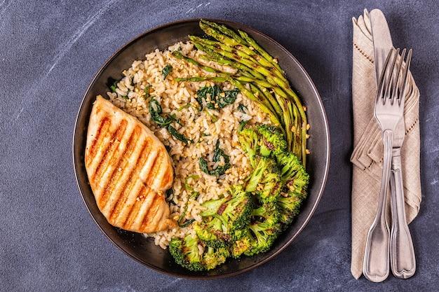 Grillowana pierś z kurczaka z brązowym ryżem, szpinakiem, brokułami, szparagami, koncepcja diety, zdrowe odżywianie.