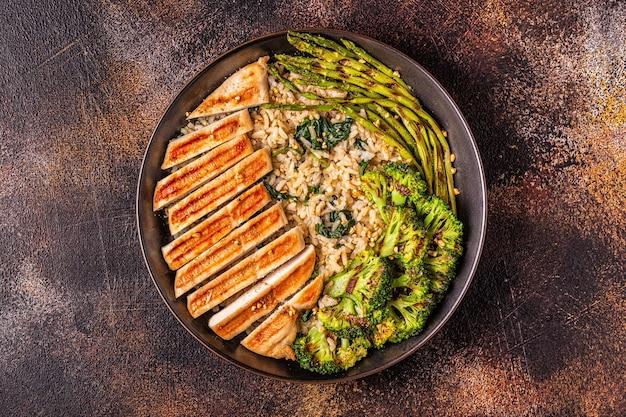 Grillowana pierś z kurczaka z brązowym ryżem, szpinakiem, brokułami, szparagami, koncepcja diety zdrowego odżywiania