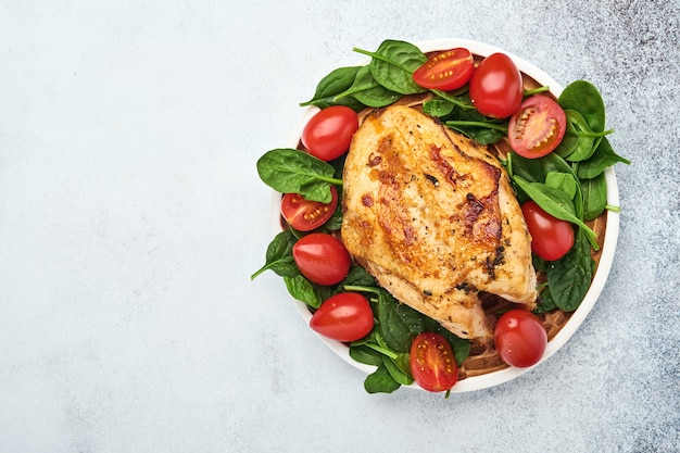 Grillowana pierś z kurczaka ze szpinakiem, zieloną sałatą, papryką i pomidorkami cherry w talerzu ceramicznym na białym tle stołu. zdrowa żywność, dieta ketogeniczna, koncepcja obiadu. widok z góry i kopiowanie miejsca