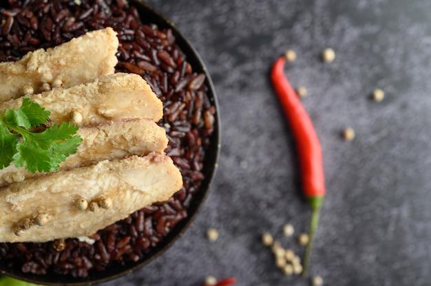 Grillowana pierś z kurczaka zwieńczona pieprzem na dojrzałych fioletowych jagodach ryżowych.