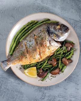 Grillowana pikantna ryba podawana ze szparagami i fasolką szparagową.kolorowa kompozycja kulinarna na talerzu. widok z góry.