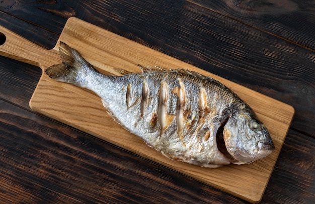 Grillowana ryba dorada na drewnianej desce