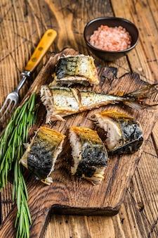 Grillowana ryba makrela pokrojona na deskę do krojenia.