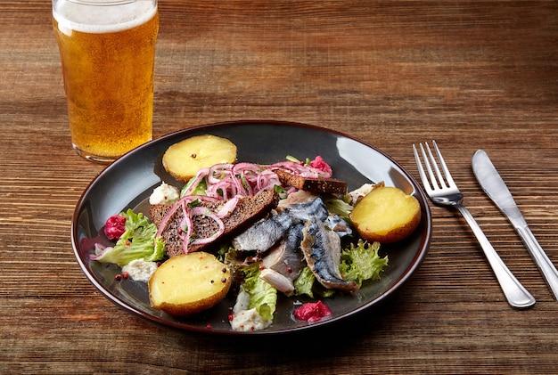 Grillowana ryba makrela z pieczonymi ziemniakami na drewnianym stole