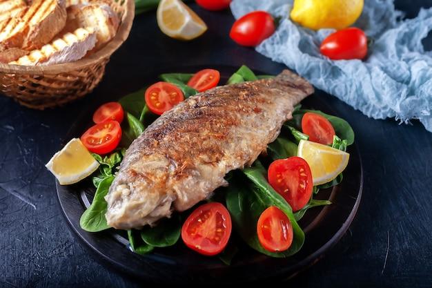 Grillowana ryba ze szpinakiem pomidorowym na drewnianej desce pyszna i lekka kolacja