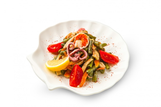 Grillowana sałatka z owoców morza i warzyw ozdobiona krewetkami, ośmiornicą i cytryną na białym tle. smażona fasolka szparagowa, papryka, marchewka i pomidory na białym tle