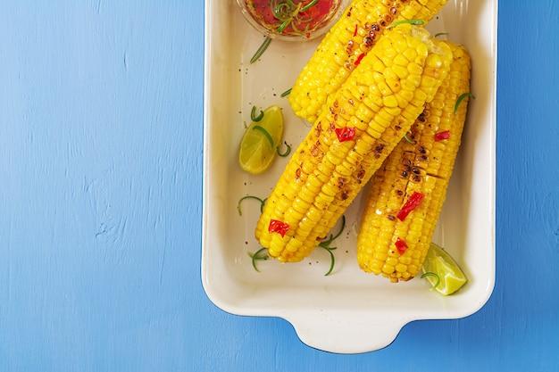 Grillowana słodka kukurydza z meksykańskim sosem, chili i limonką na niebieskim stole. zdrowe letnie jedzenie. widok z góry. leżał płasko