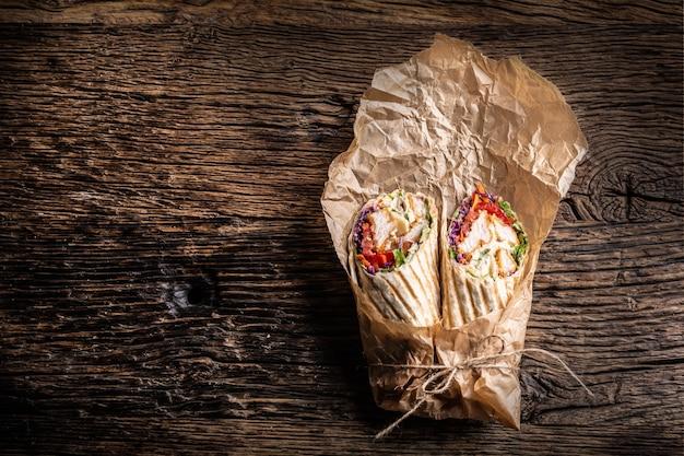 Grillowana tortilla wraps z kurczakiem i warzywami zawinięta w papier, ułożona na rustykalnym drewnie.