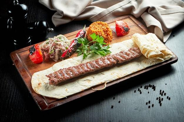 Grillowana turecka lula kebab z jagnięciny z grillowanymi warzywami, cebulą i ryżem na drewnianej desce. ciemny stół.