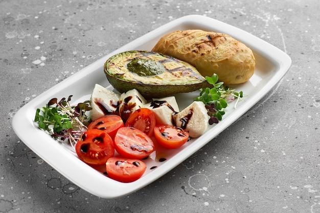 Grillowane awokado z pomidorkami koktajlowymi bazyliowym sosem pesto ser mozzarella i rukolą na białym talerzu na szarym marmurze
